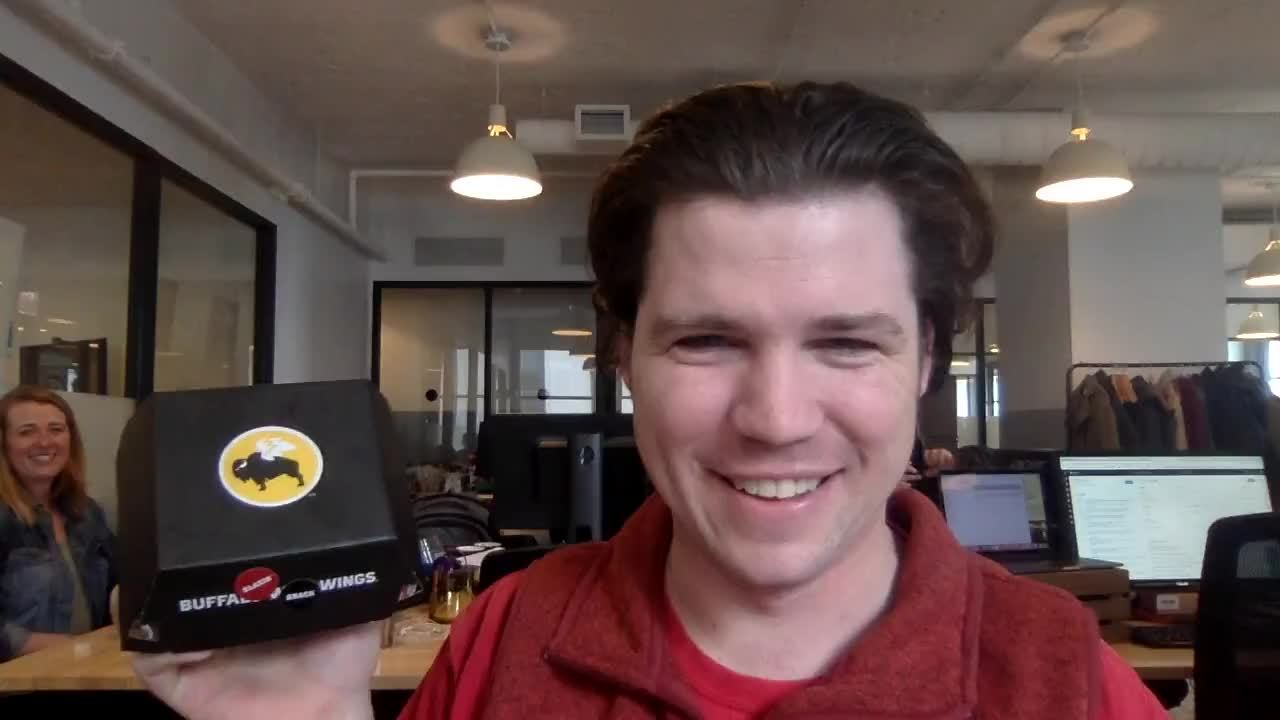 A man holding up a box of buffalo wild wings as an example of video prospecting.